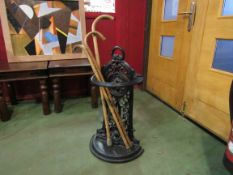 A Victorian style cast iron stick stand and three walking sticks