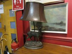 A bronzed resin table lamp base of stag form, leather shade,