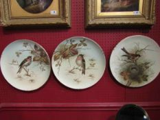 A set of three hand painted chargers decorated with birds,