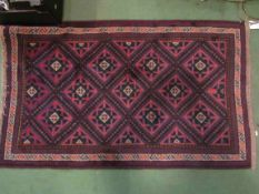 A dark red and blue ground rug with geometric borders and central diamond field,