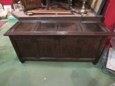 An 18th Century oak four panel hall coffer the hinged lid over turned stile feet,