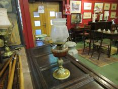 A Victorian oil lamp with glass reservoir on fluted and beaded brass base,