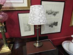A bronzed metal table lamp with cream shade,