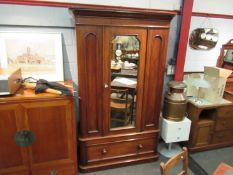 A Victorian walnut single wardrobe, the mirror door with key over a single base drawer,