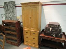 A natural pine two door wardrobe with key over two short and two long drawers,