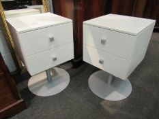 A pair of white two drawer revolving chests on circular metal bases,