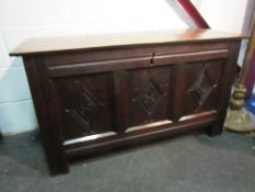 A 17th Century oak coffer, the rising lid over a carved three panel front on stile feet,