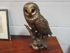 A resin owl perched on branch,