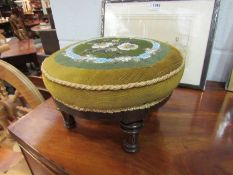 A Victorian walnut circular footstool with floral beadwork upholstery on turned and reeded feet,