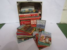 A box of books and annuals including Ladybird series