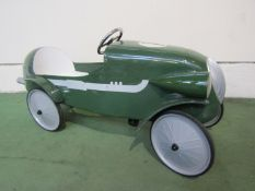 A child's green painted metal pedal racing car