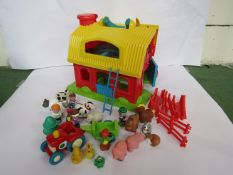A plastic model barn with a collection of farm animals,