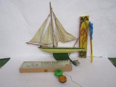 Mixed vintage toys including pond yacht, yo-yos, circus monkey,