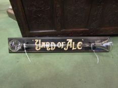 A glass yard of ale mounted on wooden board