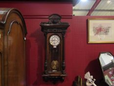 A Vienna wall clock with pendulum and two weights,