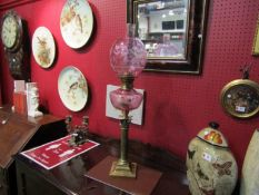 A Victorian oil lamp with pink reservoir and globular shade,