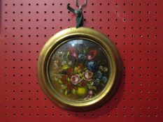 An oil on canvas of roses in cornflowers, gilt circular frame,
