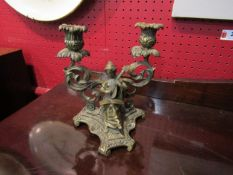 A brass twin sconce candlestick with lady playing musical instrument,