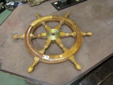 A wooden and brass ships wheel,