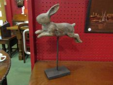 A carved wooden rabbit on stand,