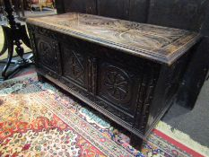 A Victorian carved oak coffer with three carved panels,