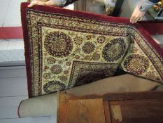 A red and cream ground rug with multiple borders,