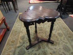 An Edwardian oak clover leaf top lamp table on turned and carved tri-legs with sledge feet base,