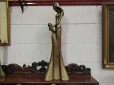 A large resin bronze figure of mother and child, repairs to base,