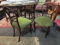 A set of four Victorian walnut balloon back dining chairs, sprung stuffed serpenetine front seats,