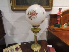 A brass effect table lamp base of oil lamp form with globular shade
