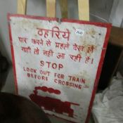 A painted metal sign for railway crossing in Indian and English.