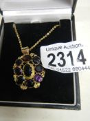 A Victorian mixed cut amethyst pendant in gold cannetille setting on yellow metal chain.