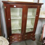 A display cabinet with 4 drawers.