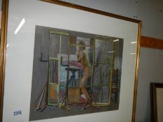 A framed and glazed S Barnes 1960's pastel drawing of a female nude in a studio behind a screen,