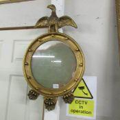 A gilt framed circular mirror surmounted eagle.