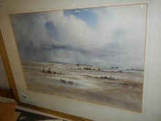 A framed and glazed water colour beach scene signed Stuart Gray.