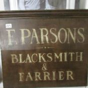 A wooden sign for F. Parsons, Blacksmith & Farrier.