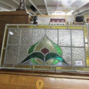 A stained and leaded glass panel. Amber rectangle on bottom corner has V crack.