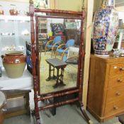 A mahogany cheval mirror.