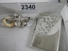 A silver cigarette case and a hall marked silver metal babies rattle.