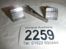 A pair of silver cuff links and a matching silver tie pin.