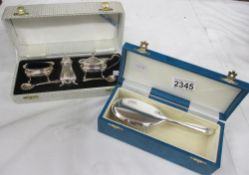A boxed silver plate cruet set and a boxed silver plate brush.