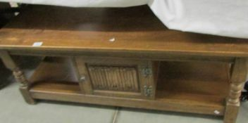 An oak coffee table with central cupboard.