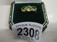 A stunning deep coloured peridot three stone ring dated London 1972 with a fancy gold work mount in