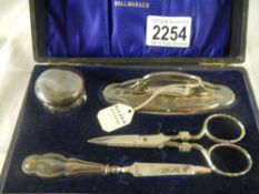 A silver manicure set. The scissors are not the correct ones for the set.