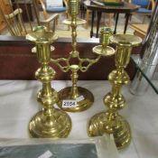 A pair of brass candlesticks and a brass candelabra.