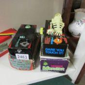 2 boxed tinplate clockwork coffin bank money boxes.