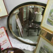 A large antique 19th century oval mirror in good order.