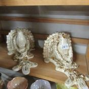 A pair of ceramic wall brackets featuring a bird on a branch in white and gold, one a/f.