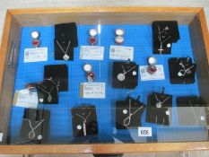 A display case containing 6 silver rings, all with certificates, and 10 silver pendants.